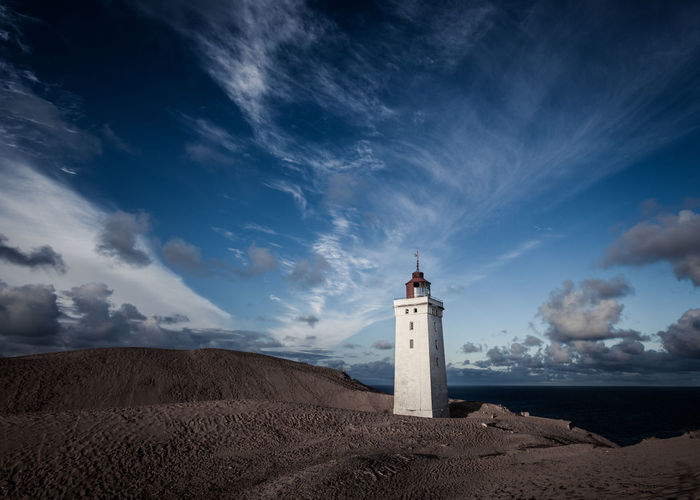 Lighthouse in sand dunes with dramatic sky