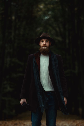 Portrait of young man wearing hat standing in forest