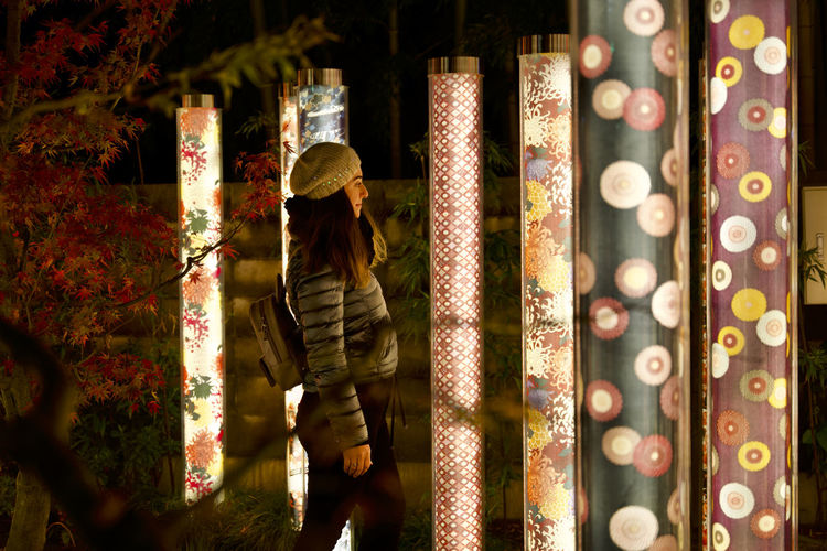 Side view of woman standing at night