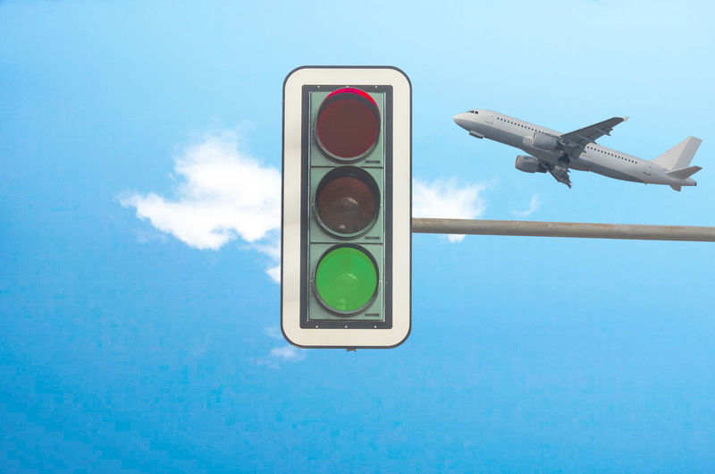 Low angle view of road signal and airplane against blue sky