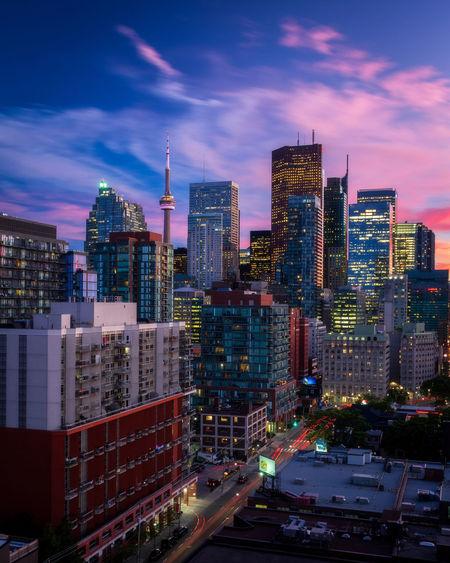 Illuminated buildings in city against cloudy sky at dusk