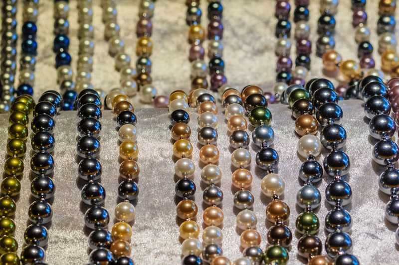 Beautiful long pearl necklaces are displayed at a jewelry shop. Poor light with noise grain shot Necklaces Abundance Arrangement Bracelet Close-up Collection Day Fashion For Sale Gemstone  Gold Colored Indoors  Jewelry Jewelry Box Jewelry Store Jewelrydesign Jewelrydesigner Large Group Of Objects Multi Colored Necklace Necklace Choker Necklace For Sale Necklacehomemade No People Ornament Pearl Pearl Necklace  Pearl Necklaces Pearls Retail  Shiny Still Life Variation Wealth