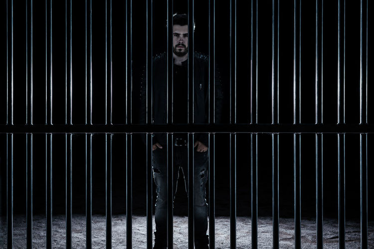 Portrait Of Man Standing By Metal Grate In Darkroom