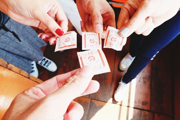 Low section of friends holding tickets on hardwood floor in ferry