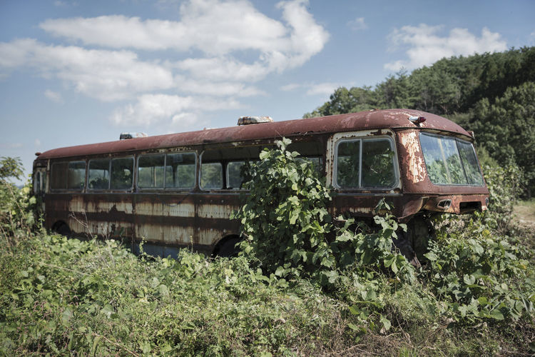 Abandoned bus on field against sky