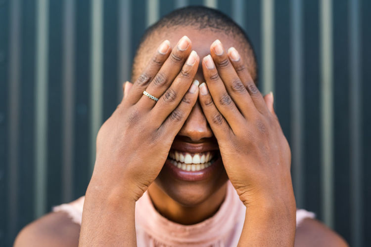 Close-up of laughing woman covering face