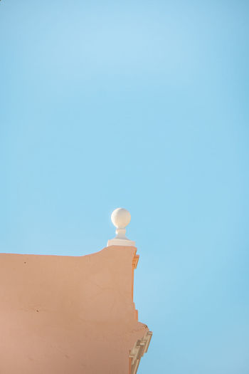 Low angle view of balloons against building against clear blue sky