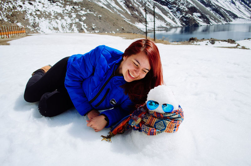 Young woman lying down on snow covered land