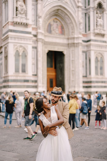Young couple embracing while standing against building