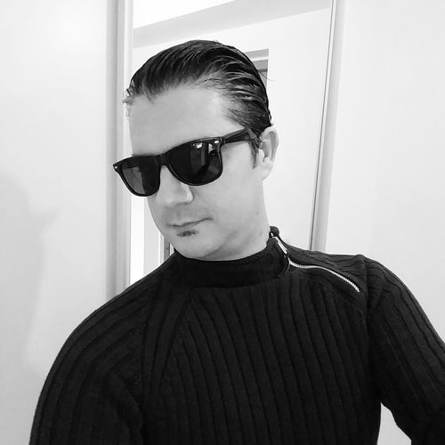Portrait of young man wearing sunglasses standing at home