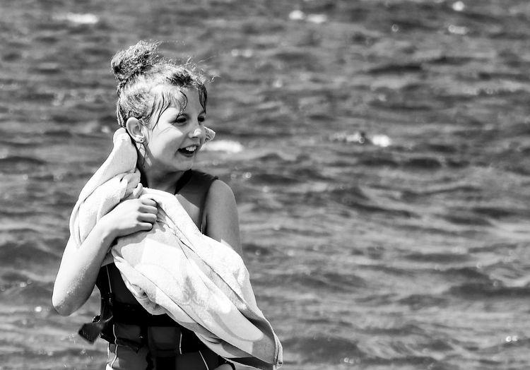 Portrait Of Happy Girl Standing In Sea