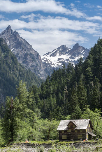 Log Cabin Against Trees And Mountains Against Cloudy Sky