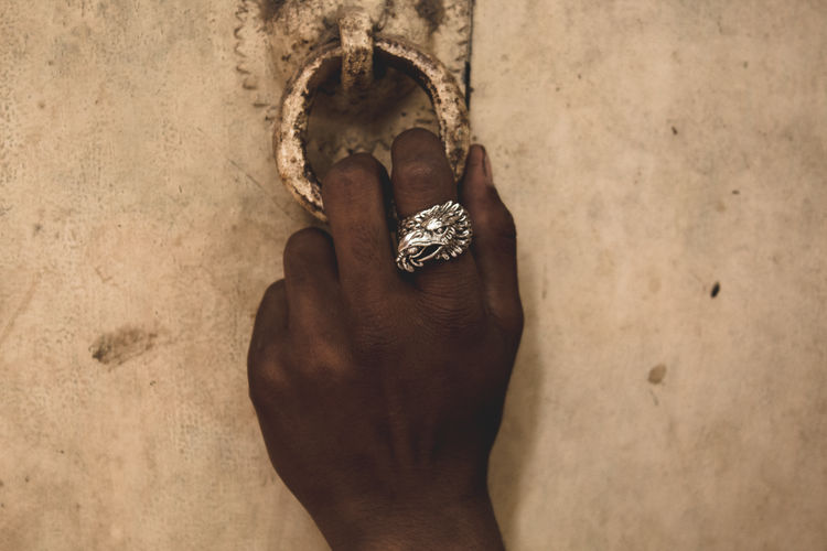 Close-up of woman hand holding door knocker