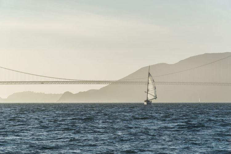 Suspension bridge over sea against clear sky