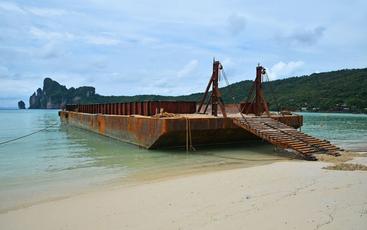 Old rusty corroded cargo barge in the bay ofPhi Phi Don island Ark Barge Beach Cargo Corrosion Ferry Industrial Island Landscape Landscapes With WhiteWall Load Old Phi Phi Ramp Rusty Sand Sea Seashore Ship Spotted In Thailand