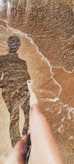 High angle view of feet on sand at beach