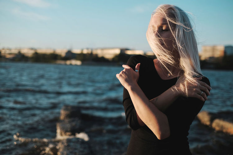 Woman with tousled hair standing against sea during sunset