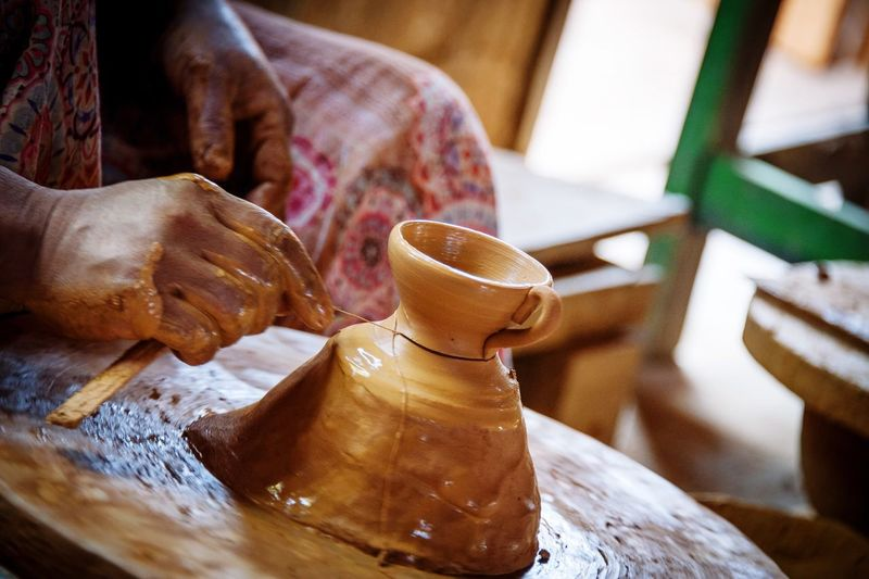Midsection Of Woman Making Pot