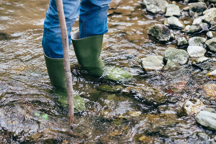 Body Part Boot Casual Clothing Day Human Body Part Human Leg Jeans Lifestyles Low Section Mud Nature Occupation One Person Outdoors Real People Rubber Boot Standing Stream - Flowing Water Water Waterfront Working