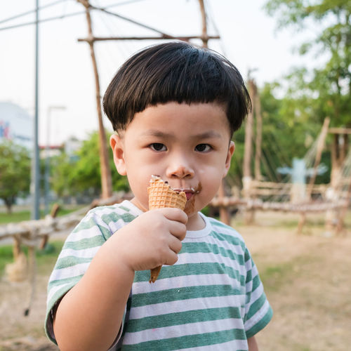 happy kid boy eating ice cream in the park Boys Casual Clothing Child Childhood Dairy Product Eating Focus On Foreground Food Food And Drink Front View Holding Indulgence Innocence Men One Person Outdoors Portrait Real People Sweet Sweet Food Temptation Waist Up