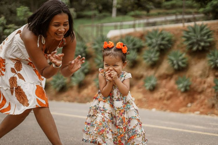 Happy mother and daughter laughing on road