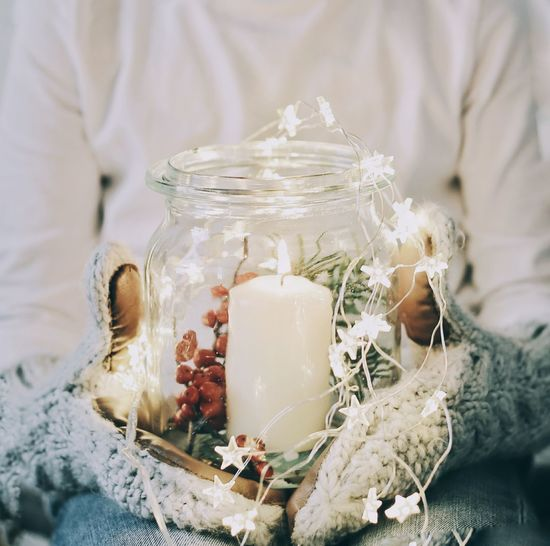 Midsection of person holding christmas candle