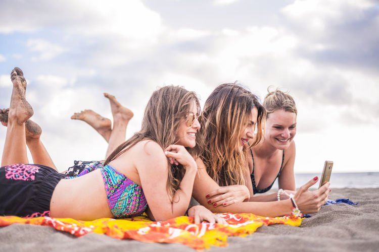 Happy friends taking selfie with smart phone while lying at beach