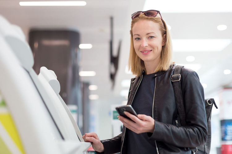Portrait of beautiful woman using atm at airport