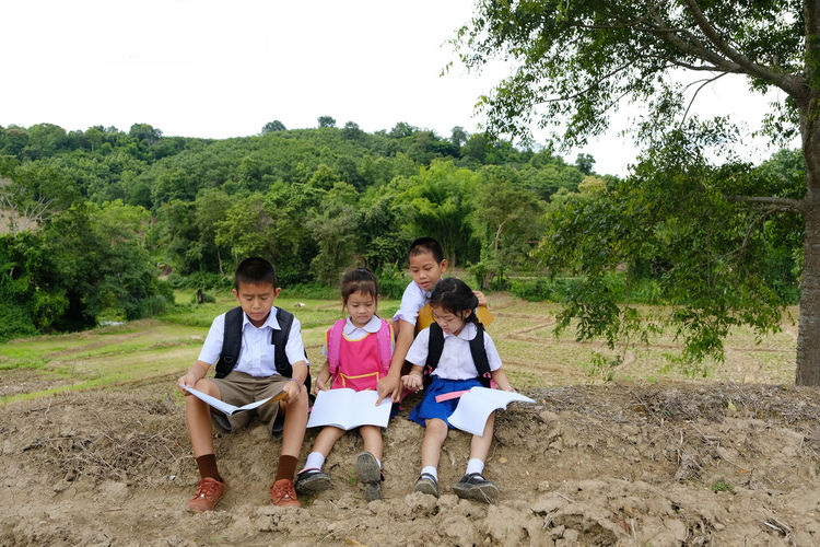 Siblings in school uniforms reading while sitting on field against trees