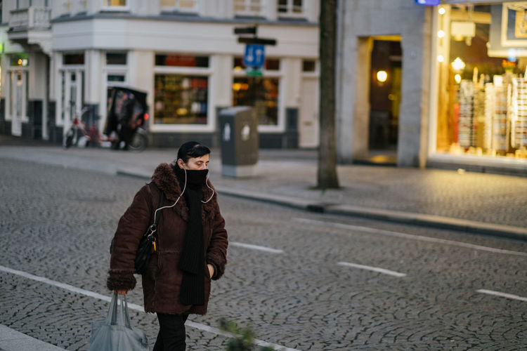 Man standing on street in city during winter