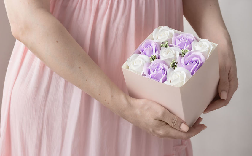 Midsection of woman holding pink flower against white wall
