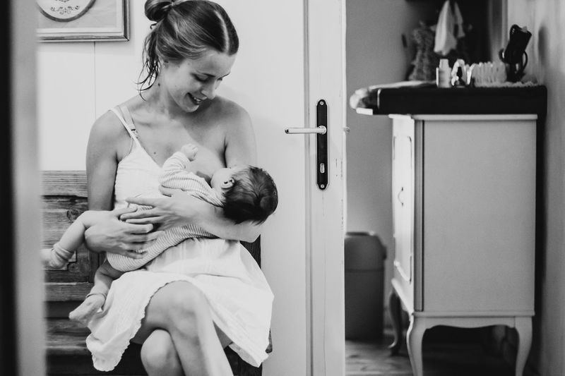 Smiling Mother Breastfeeding Daughter At Home