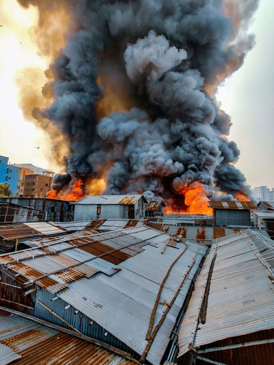 Fire by buildings against sky