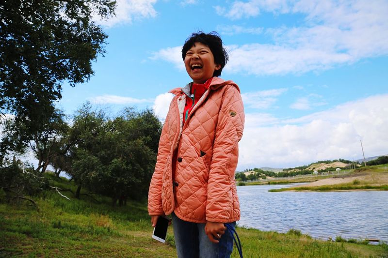 Cheerful Woman Laughing At Riverbank Against Sky