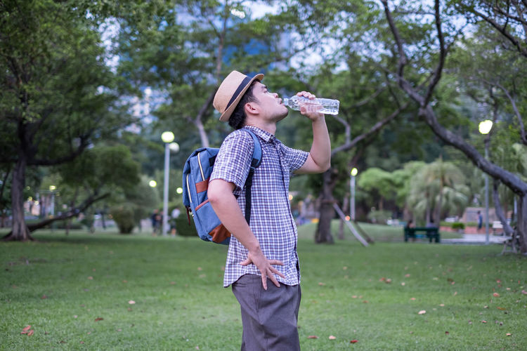 asian young man age 25-30 year tourists backpacker. he was thirsty and was drinking water from a plastic bottle. during travel the holidays and relax.water Water Man Drinking Drink Young Adult Healthy Sport Bottle Portrait Men Lifestyles Males  person Outside Summer Caucasian Attractive Fitness Training Nature Health Outdoor Thirsty  Fit Muscular Thirst Masculine Business Workout Modern Mineral Spring Terrace Guy Hair Life Cheerful Travel Tourist Vacation Tourists Tourism Traveler Traveling Thailand Holiday Backpack One Person Grass Real People Holding Park