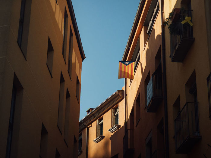 Low angle view of buildings with a catalan flag hanging out of the window against clear sky