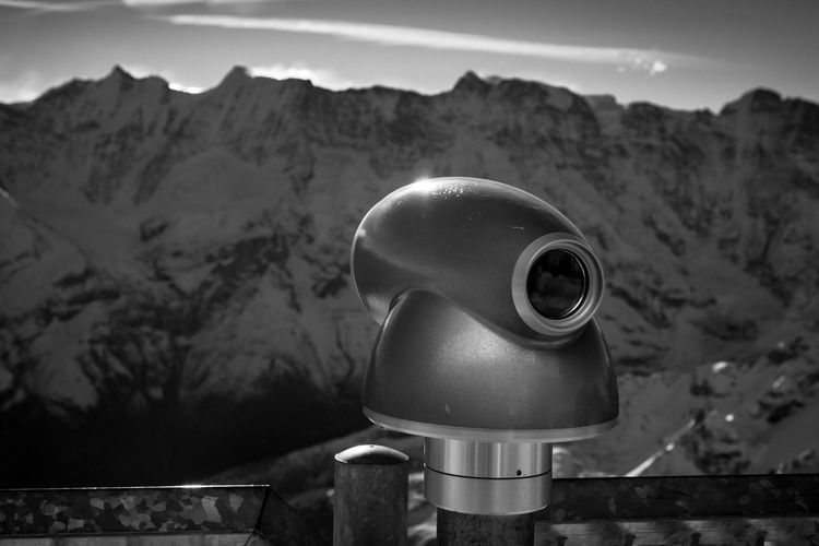 Close-up of coin-operated binoculars against mountains