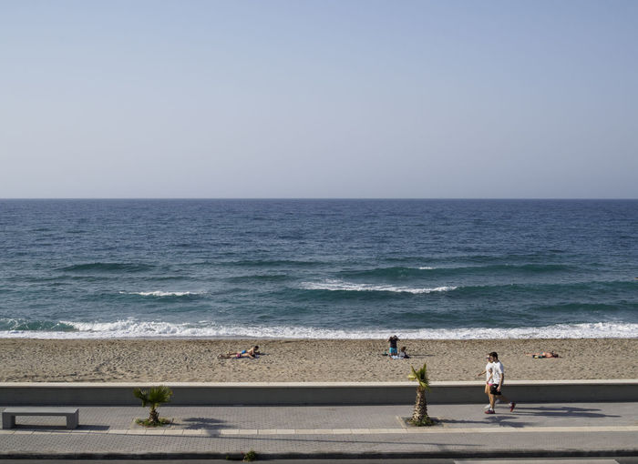 people walking on the pavement in front of the beach at Rethymno Crete in the afternoon Beach Clear Sky Horizon Over Water People Sea Shadows Streetphotography Two People Vacations Walking Water