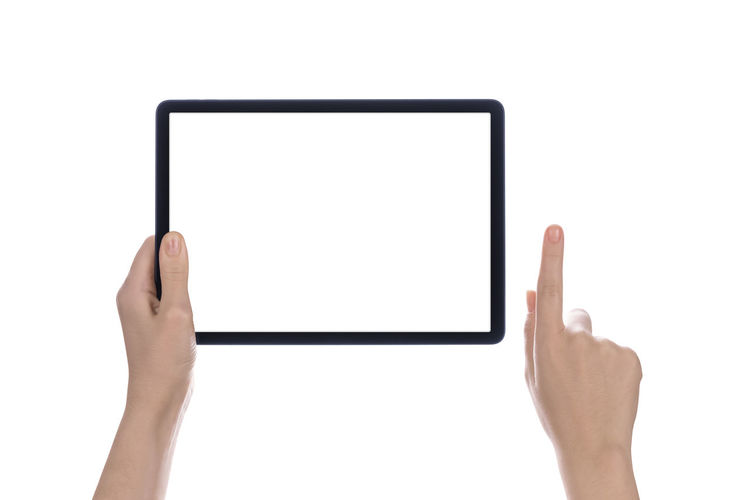 Low section of person holding mobile phone against white background