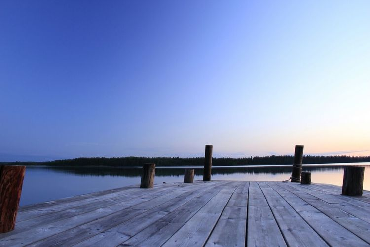 Pier over calm lake against clear sky