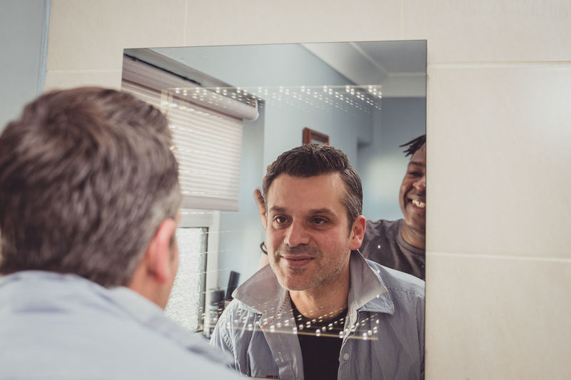 A gay couple together in front of the bathroom mirror. Men Males  Indoors  Adult People Gay Couple Lgbtq Homosexual Love Mirror Bathroom Home Interior Indoors  Love Admiration Romance Evening Out Teasing Gay Couple Husband Boyfriend Smiling Young Adult Fun Playful
