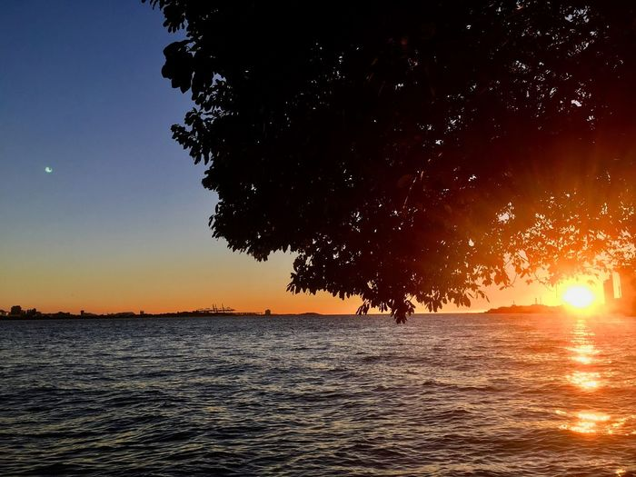 Goodbye🌞 Sky Water Sunset Scenics - Nature Nature Beauty In Nature Tranquility Orange Color Tranquil Scene Sun Idyllic Sea Waterfront Silhouette No People Outdoors Sunlight Splashing Tree