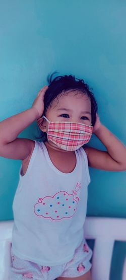 Cute baby girl wearing mask standing on chair against wall