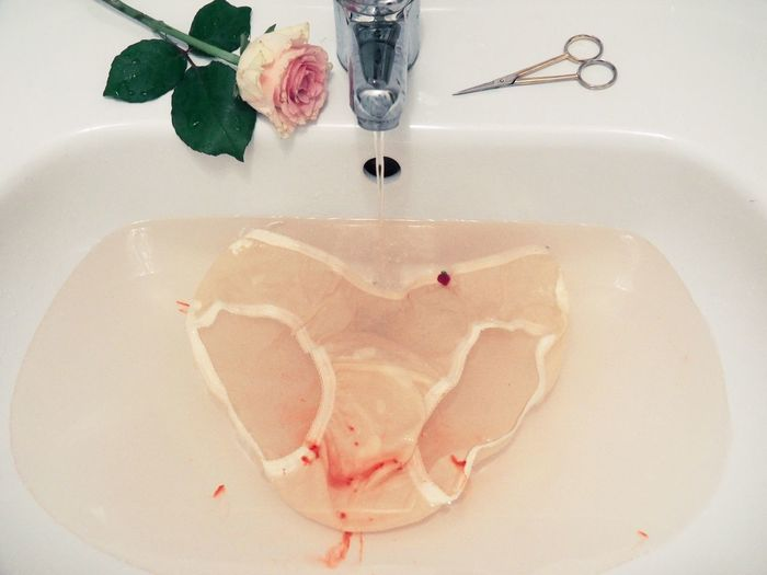 Stained underwear under running water in sink