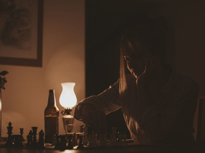 Close-up of illuminated woman sitting at table in restaurant