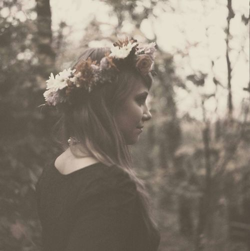 Smiling Beautiful Woman Wearing Floral Garland In Forest