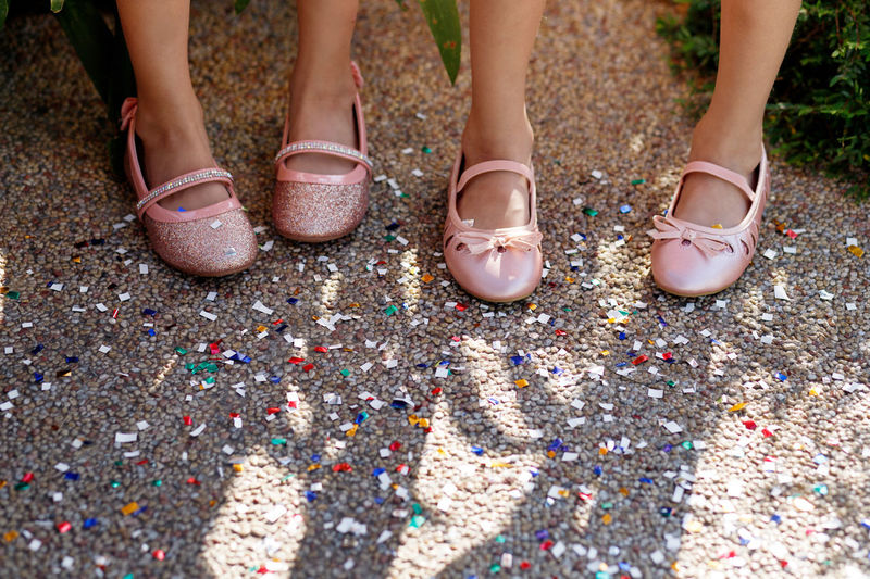 Low section of female friends wearing shoes while standing on colorful confetti