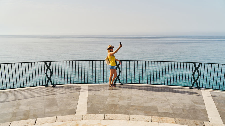 Rear view of woman standing by swimming pool against sea