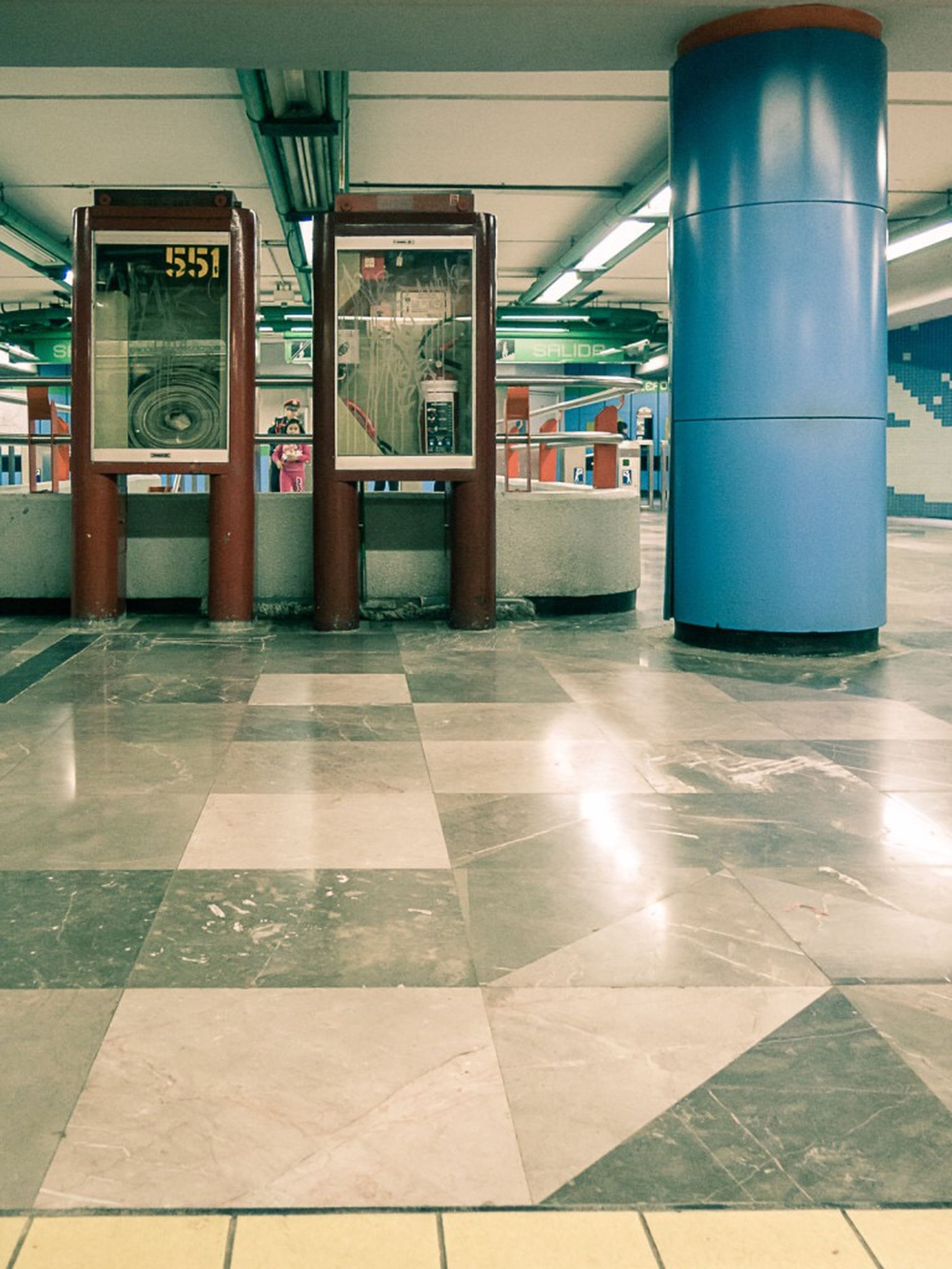 indoors, tiled floor, architecture, built structure, flooring, empty, illuminated, railroad station, architectural column, tile, absence, reflection, incidental people, public transportation, transportation, interior, railroad station platform, ceiling, column, door