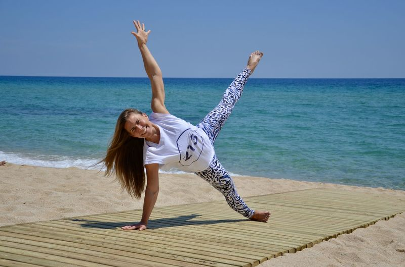 Full Length Portrait Of Woman Exercising By Sea